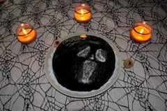在蜘蛛网桌布的万圣夜蛋糕与蜡烛 图库摄影