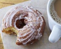 在蜡纸的给上釉的油煎饼多福饼在一个杯子热的咖啡旁边 免版税库存图片
