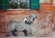 在蝶形领结的一条狗-在一个砖房子的墙壁上的老街道画在Castello区 免版税库存图片