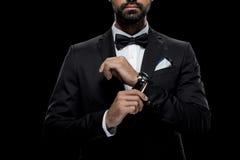 在蝶形领结的有手表的商人和无尾礼服,隔绝在黑色 免版税库存图片
