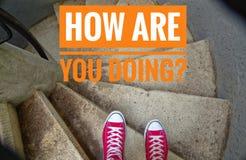 在螺旋形楼梯,当去下坡和时题字的红色运动鞋用英语怎么是您做?用德语Wie geht ES weite 免版税库存图片