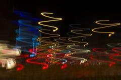 在螺旋的行动的色的光在作为抽象backgrou的晚上 免版税库存图片