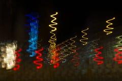 在螺旋的行动的色的光在作为抽象backgrou的晚上 库存图片