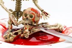 在血液的静物画骨骼与在白色背景的刀子 免版税图库摄影