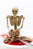 在血液的静物画骨骼与在白色背景的刀子 免版税库存照片