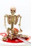 在血液的静物画骨骼与在白色背景的刀子 库存照片