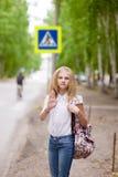 在行人交叉路附近的女孩少年陈列开放手 免版税库存照片