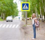在行人交叉路附近的少年常设女孩 免版税库存照片