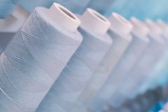 在行企业工厂概念想法的五颜六色的螺纹在蓝色口气背景中 库存图片