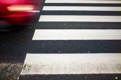在行动和行人交叉路的红色汽车 免版税库存照片