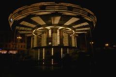 在行动的发光的黄色儿童` s转盘,在晚上 免版税库存图片