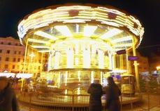 在行动的发光的黄色儿童` s转盘,在晚上 免版税图库摄影
