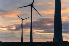 在行动的巨大的风车在日落 免版税库存照片