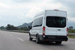 在行动的旅游小巴在背景山 免版税库存照片