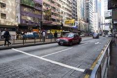 在行动的红色出租汽车在街道上 库存图片