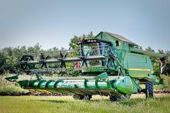 在行动的联合收割机对麦田 免版税图库摄影