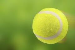 在行动的草地网球运动球在绿色背景 库存照片