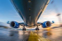 在行动的飞机在起飞和着陆期间,在日落和湿跑道背景  免版税库存照片