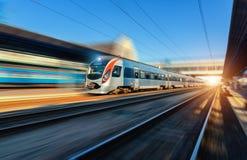 在行动的高速火车在日落的火车站 免版税图库摄影