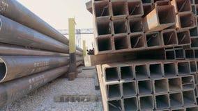 在行和管子放置的金属外形在开放金属仓库里,大金属外形在仓库里 股票视频