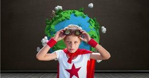 在行星地球世界前面的超级英雄男孩有黑板背景 库存图片