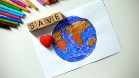在行星绘画,生态概念,世界的保存词和心脏标志在家 免版税库存图片