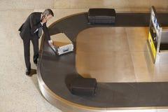 在行李转盘的商人要求的手提箱在机场 库存图片