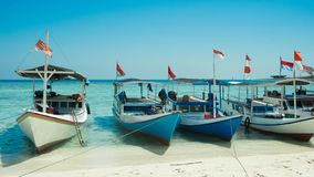 在行的一条传统小船与木材料和印度尼西亚旗子 免版税库存照片