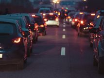 在行的堵车汽车在高速公路黄昏夜 库存图片