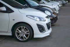 在行的汽车在汽车停车处前面 免版税库存图片