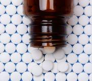 在行的阿斯匹灵与在上面的瓶 免版税库存照片