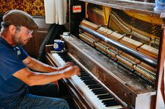 在街市旅馆里面的钢琴人在道森市,育空 免版税库存照片