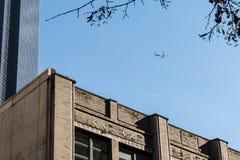 在街市西雅图的商业飞机飞行被看见在一些个摩天大楼之间 库存图片
