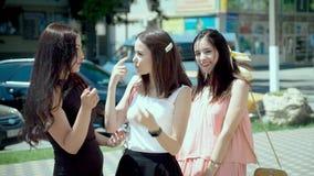 在街道上一起会集的三名时髦的妇女,笑了并且聊天了 影视素材