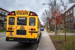 在街道上停放的北美洲黄色学校班车,有通过的汽车的等待的学生  图库摄影