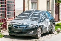 在街道上停放的损坏的新的黑欧宝雅特J斜背式的汽车盖和保护与在残破的挡风玻璃的尼龙免受rai 库存图片
