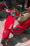 在街道上停放的红色减速火箭的意大利样式滑行车 免版税图库摄影