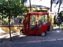 在街道上停放的红色电自行车 免版税库存图片