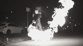 在街道上的一个人倾吐从一台火焰喷射器的火用不同的方向 在慢动作的凉快的计划 影视素材