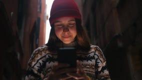 在街道上的一个妇女身分和看手机屏幕 光照亮她的面孔 股票录像