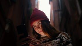 在街道上的一个年轻女人身分和看手机屏幕 光照亮她的面孔 股票录像