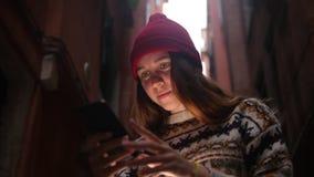 在街道上的一个年轻微笑的妇女身分和看手机屏幕 光照亮她的面孔 股票视频
