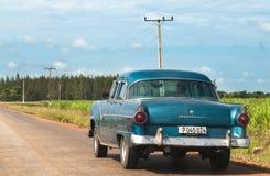 在街道上的一位绿色经典汽车司机在国内 免版税库存图片