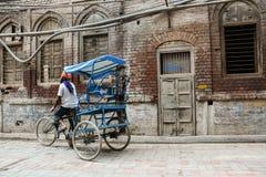 在街道上的一辆人骑马三轮车在老德里,印度 免版税图库摄影