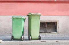 在街道上的两个绿色塑料垃圾箱有收集垃圾的破烂物和废弃物等待的大型垃圾桶卡车的 库存照片
