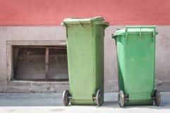 在街道上的两个绿色塑料垃圾箱有收集垃圾的破烂物和废弃物等待的大型垃圾桶卡车的 免版税库存照片
