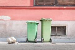 在街道上的两个绿色塑料垃圾箱有收集垃圾的破烂物和废弃物等待的大型垃圾桶卡车的 免版税图库摄影
