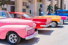 在街道上的五颜六色的美国经典汽车在哈瓦那,古巴 免版税图库摄影