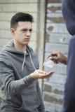 在街道上的十几岁的男孩买的药物从经销商 免版税库存图片