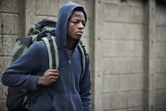 在街道上的十几岁的男孩有背包的 免版税库存照片